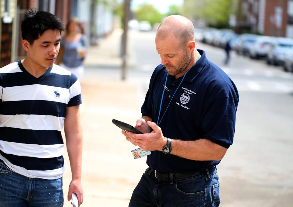 Contractor Wei Huang watched as inspector John Lyons worked on his tablet, which replaced a bulky laptop.
